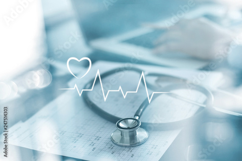 Stethoscope with heart beat report and doctor analyzing checkup on laptop in health medical laboratory background Fotobehang