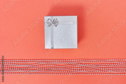 Fotografia  Bright silver closed gift box on paper background living coral colored
