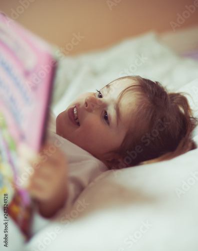 Fotografía  Little girl reading book in bed.  Focus on background.