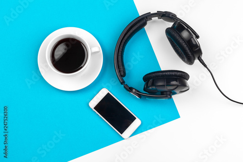 Fototapeta Headphones and coffee cup on blue background, top view obraz na płótnie