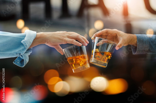 Carta da parati Close-up of two men clink glasses of whiskey drink alcoholic beverage together w