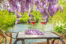 Beautiful Still Life With Glasses Of Pink Wine On The Vintage Table Above The Blooming Purple Wisteria Near The River On Sunny Day