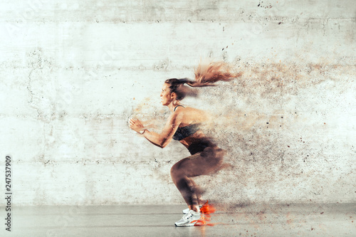 Fotografiet  Side view of muscular focused brunette with ponytail and in sportswear jumping in front of brick wall in gym