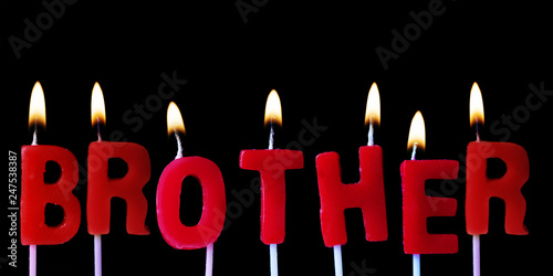 Photo Brother spellt out in red birthday candles against a black background