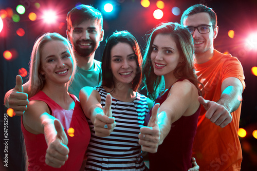 Fotografia  People showing OK sign in the night club