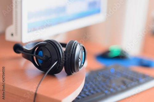 Big black headphones lie on the wooden desktop of the sound designer - 247564550