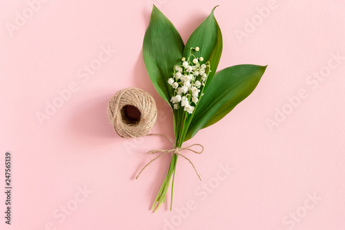 Bouquet of lilies of the valley with green leaves tied with twine