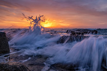 Amazing Splash Of Seawater At Sunrise On The Shore Of The Black Sea. Beautiful Motion Blur Sea Waves Over The Rocks. Low Angle View