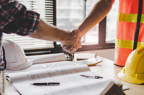 construction worker team hands shaking after consultation meeting to greeting start up plan new project contract in office center at construction site, teamwork, partnership and contractor concept