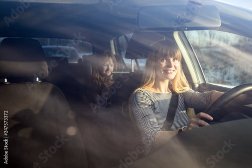 Fototapeta Mom driving car while her daughter sitting on back seat and using digital tablet