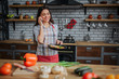 Cheerful nice woman stand in kitchen and talk on phone. She smiles. Woman hold frying pan with food. Vegetables lying on desk with knife.