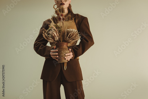 Poster Animaux de Hipster cropped view of stylish woman holding clay jug with dry flowers isolated on beige