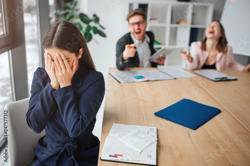 Young woman hurt by rude colleagues Fototapet