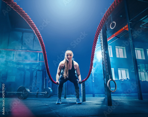 Poster Fitness Woman with battle rope battle ropes exercise in the fitness gym. CrossFit concept. gym, sport, rope, training, athlete, workout, exercises concept