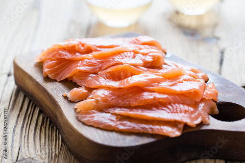 Smoked salmon on wooden board, sliced Fotobehang