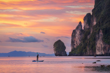Sunset Phi Phi Island Loh Dalum Beach With Man On SUP Board And Limestone Rocks On Background