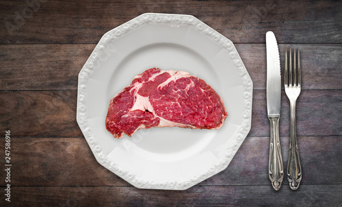 red meat / raw steak on plate on wooden background with knife and fork - Fototapeta