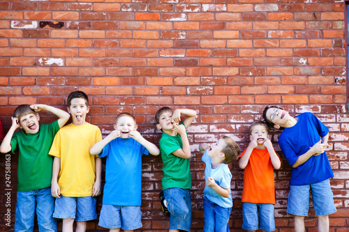 Group of Boys Making Faces by Brick Wall Outside Wallpaper Mural