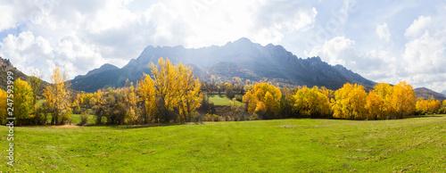 Aluminium Prints Autumn Vista panoramica de Paisaje otoñal de prados verdes arboledas y montañas rocosas al fondo. Con pequeño pueblo escondido entre los arboles