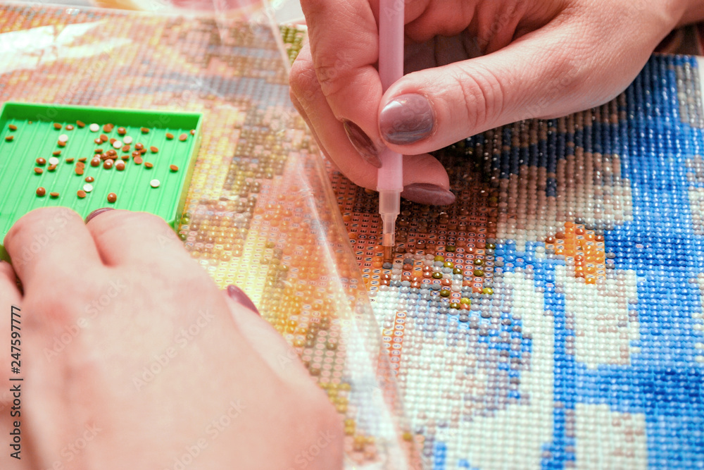 Fototapety, obrazy: Girl collect diamond painting. Diamond embroidery with a pen. Closeup, selective focus