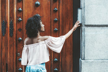 Side View Of A Dazzling African-American Girl With A Curly Afro Hair That Is Pushing A Button Of The House Intercom Outdoors In Front Of A Huge Wooden Antique Door With Steel Forged Patches