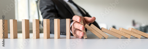 Fotografia  Business mediator stopping falling wooden dominos with his hand