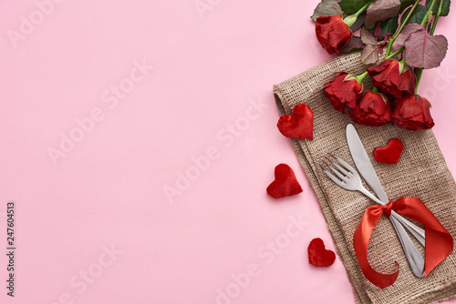 Romantic dinner. Close up of table setting with fresh red roses and decorative hearts