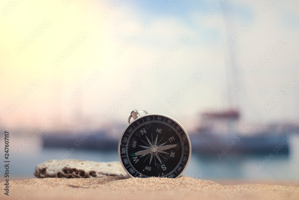 Fototapety, obrazy: Time to travel. An idea for tourism with a compass in the sand with corals in the background of the sea and a parking for yachts.