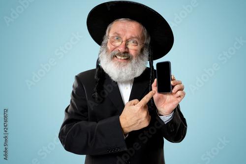 Fototapeta Portrait of old senior orthodox Hasdim Jewish man with mobile phone at Jewish festival of Purim at studio. The purim, jewish, festival, holiday, celebration, judaism, tradition, business obraz