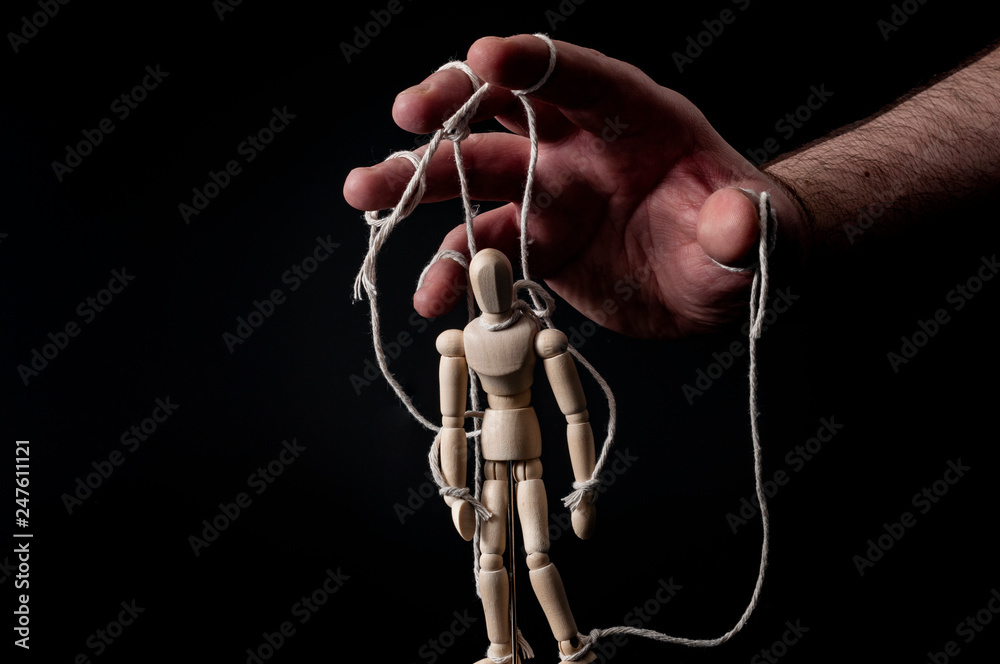 Fototapeta Employer manipulating the employee, emotional manipulation and obey the master concept with ominous hand pulling the strings on a marionette with moody contrast on black background