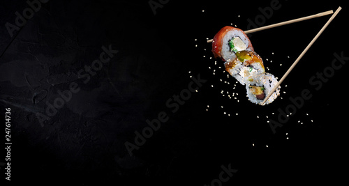 Printed kitchen splashbacks Sushi bar Sushi pieces placed between chopsticks, separated on black background. Traditional japanese food