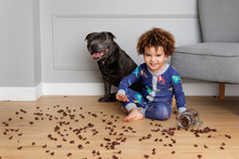 Mischievous Boy And Dog Making Mess With Cereals On Floor
