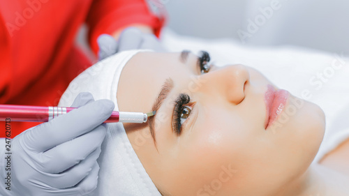 Photo  Beautiful young girl with long eyelashes tweezing her eyebrows in a beauty salon
