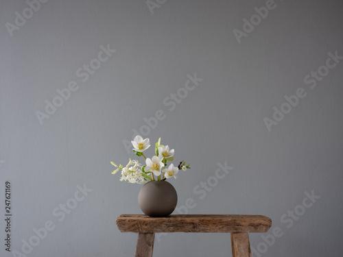 Kleine runde Keramikvase auf einem alten Vintage-Schemel mit Blumen im Frühling