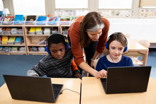 Teacher Helping Students With Laptop Computers