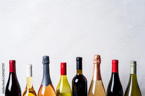 Photo Tops from different kinds new bottles of champagne, white, red wine on light bac