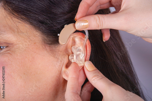 Valokuva  Close up of hands inserting hearing aid in ear