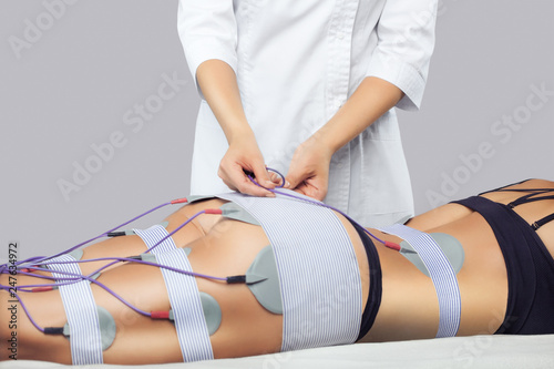 Photo  The procedure of myostimulation on the legs and buttocks of a woman in a beauty salon