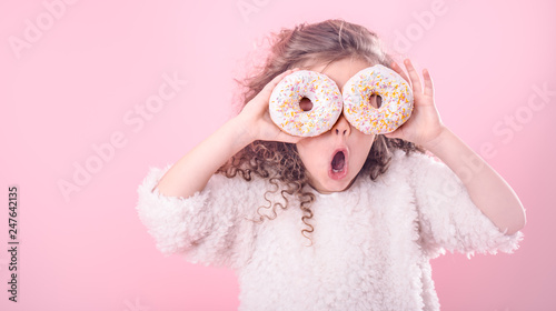Valokuva  Portrait of a little surprised girl with donuts