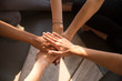 Top view of women stack hands engaged in teambuilding activity