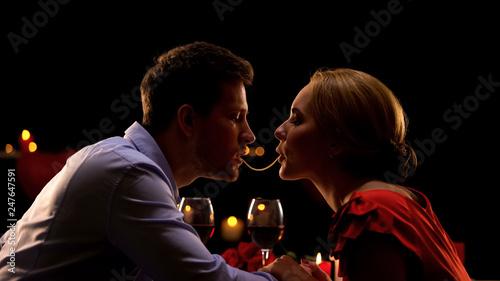 Fotografía  Beautiful couple making spaghetti kiss on romantic date in restaurant, love