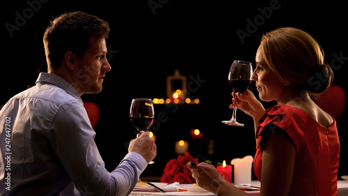 Male and lady having dinner in restaurant tasting red wine, couple on blind date Canvas Print