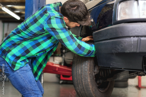 Fotografía  Mecanic checking car suspension system, at repair service station