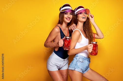 Two sensual young women in summer outfits, cap, swimsuits holding jars with fresh beverages while standing on bright yellow background