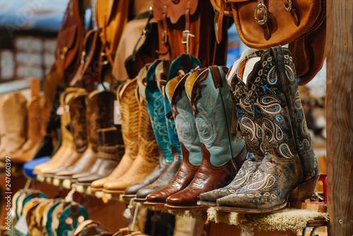 Fényképezés  Stylish western boots on a shelf in a store