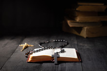 Open Book Of Bible And Crucifix On Dark Table. Low-key Image Of New Testament, Cross And Rosary In Bright Light Among Darkness And Shadows With Copy Space