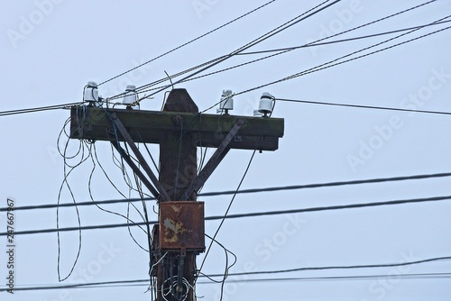 Fotografie, Obraz  one old gray wooden pole and electrical wires against the sky