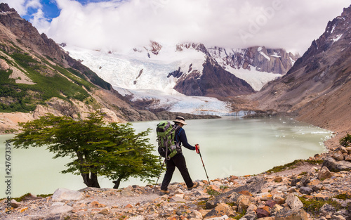 Young man walking up to mount Torre view point next to a lake or lagoon, with a green backpack on, on a summer sunny day with mountains and a glacier, near campsite De Agostini, El Chalten, Patagonia