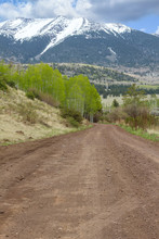 Empty Dirt Road Through Snow Capped Mountain In Rockies