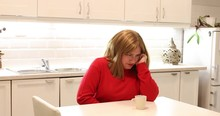 Portrait Of A Woman Sitting In The Kitchen  And Having Strong Stomach Ache  Hands On Abdomen